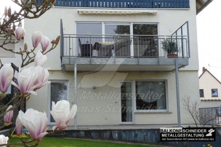 Metallbalkon mit glattem Unterboden und seitlichem Geländer als Sicht- und Windschutz.