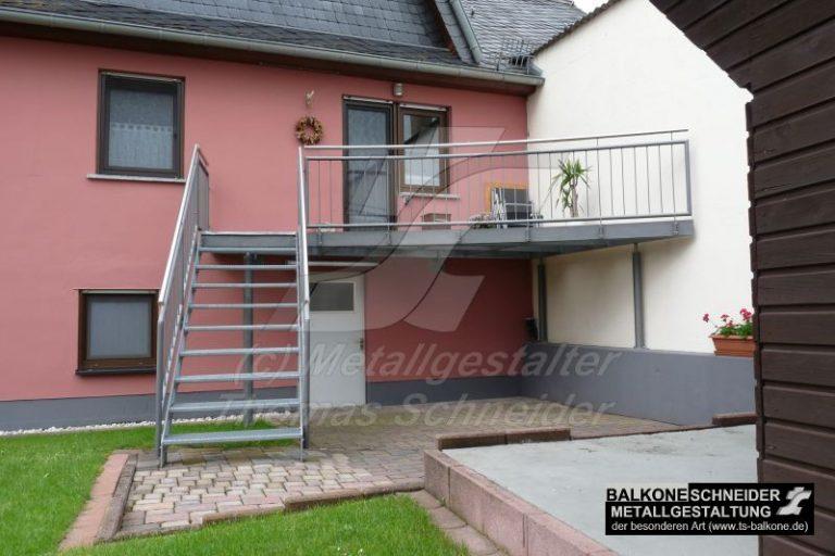 Dieser Freisitz mit Blick in den Garten besticht durch ein schlichtes Balkongeländer. Die Treppe führt vom Garten direkt auf den dynamischen Metallbalkon.