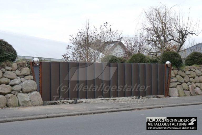 Hoftor in Natursteinmauer integriert.
