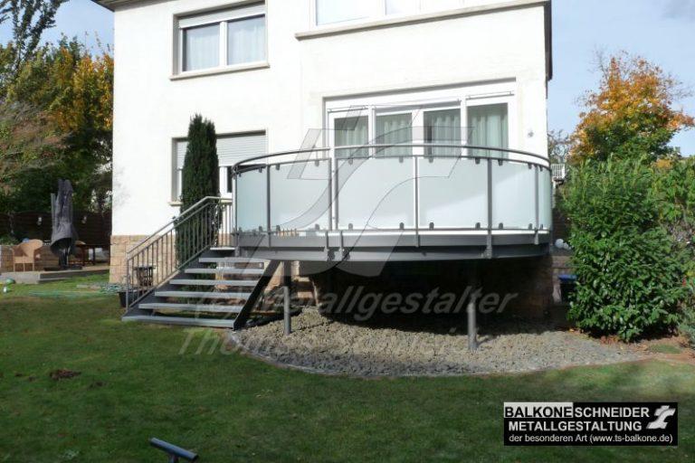 Sie wünschen etwas Außergewöhnliches? Eine Treppe die sich zum Garten verbreitert. Das Geländer ist mit gerundeten Sicherheitsglasscheiben ausgestattet.